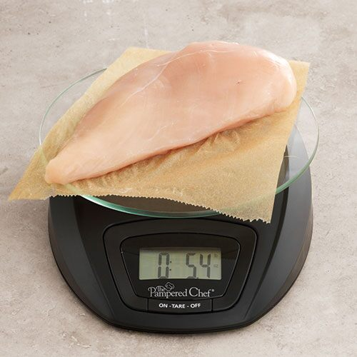 Kitchen scale measuring chicken breast.